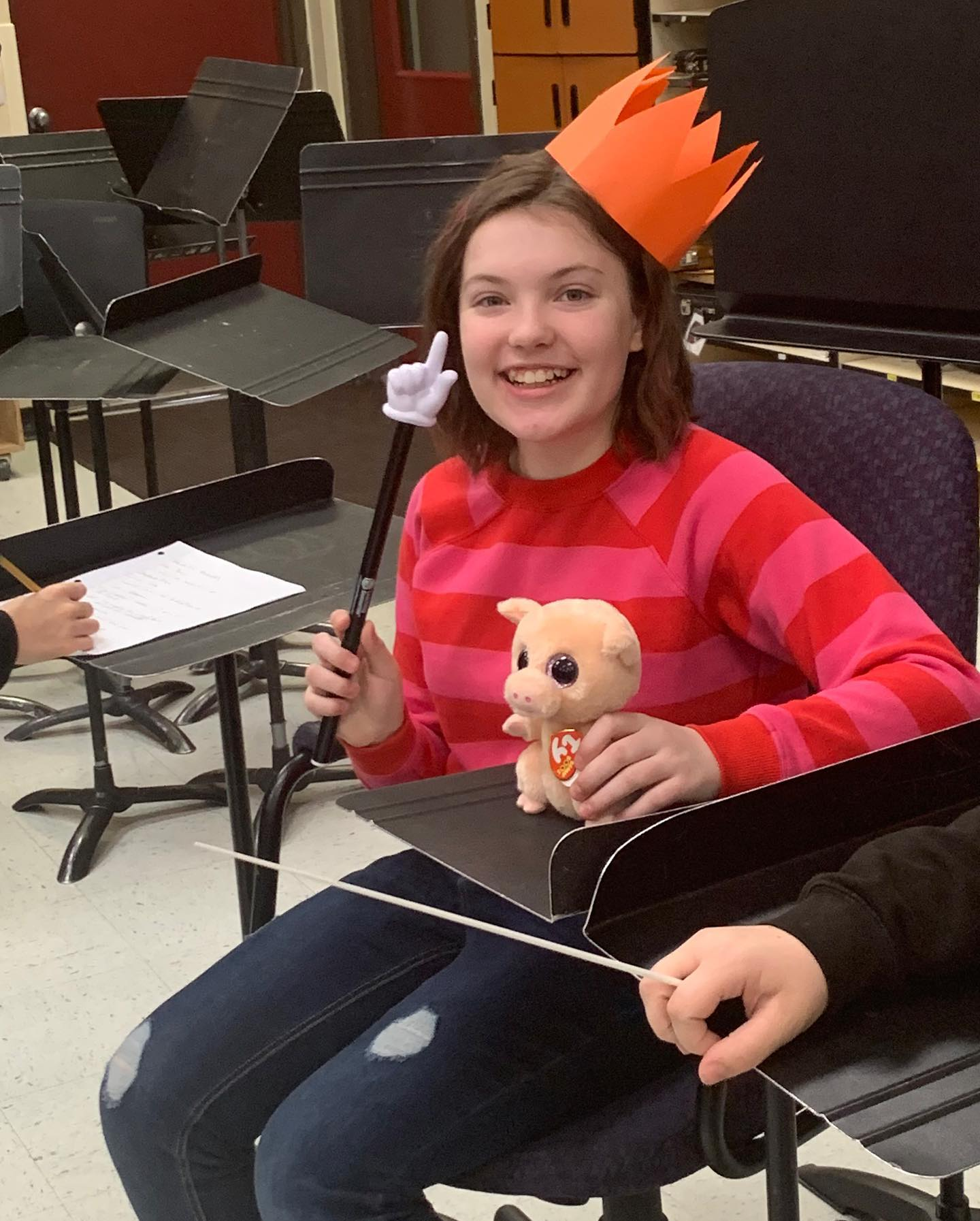 student holding finger wearing crown in band class